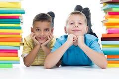 Studenti che si siedono dietro il mucchio dei libri sul fondo bianco Fotografia Stock