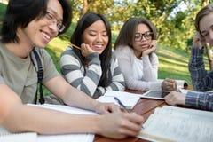 Studenti che si siedono e che studiano all'aperto mentre parlando Immagini Stock