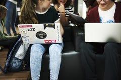 Studenti che si siedono facendo uso dell'e-learning con il computer portatile Immagini Stock Libere da Diritti