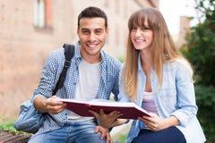 Studenti che si siedono lettura all'aperto un libro Fotografie Stock Libere da Diritti