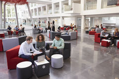 Studenti che si siedono nell'atrio dell'università, tre in priorità alta fotografia stock
