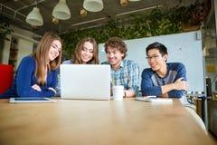 Studenti che si siedono nell'aula e che per mezzo del computer portatile Immagini Stock