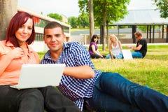 Studenti che si siedono nell'erba, imparante Fotografie Stock