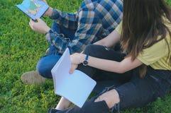 Studenti che si siedono sull'erba vicino all'istituto universitario Adolescenti che preparano agli esami Fotografia Stock