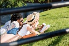 Studenti che si trovano sull'erba verde mentre studiando nel parco Immagini Stock