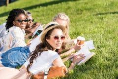 Studenti che si trovano sull'erba verde mentre studiando nel parco Fotografia Stock