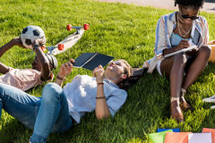 Studenti che si trovano sull'erba verde mentre studiando nel parco Fotografia Stock Libera da Diritti