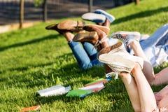 Studenti che si trovano sull'erba verde in parco Immagini Stock Libere da Diritti