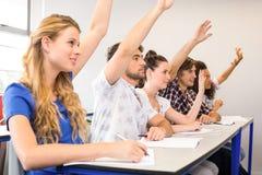 Studenti che sollevano le mani in aula Fotografie Stock