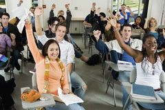 Studenti che sollevano le mani nell'aula Immagine Stock