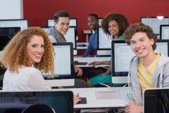 Studenti che sorridono alla macchina fotografica nella classe del computer Immagini Stock