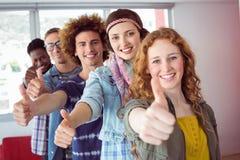 Studenti che sorridono in singola linea con i pollici su Fotografia Stock Libera da Diritti
