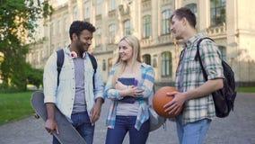 Studenti che stanno istituto universitario vicino, chiacchieranti e flirtanti Ragazzo di scelta biondo video d archivio
