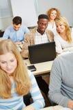 Studenti che studiano con il computer portatile Fotografia Stock
