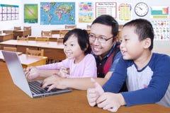 Studenti che studiano con il loro insegnante e computer portatile Fotografia Stock