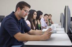 Studenti che studiano mentre sedendosi nel laboratorio del computer Immagini Stock Libere da Diritti