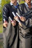 Studenti che tengono i diplomi sul giorno di laurea dentro Fotografie Stock