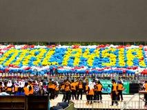 Studenti che tengono le bandiere e che celebrano Hari Merdeka Immagine Stock