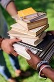 Studenti che tengono mucchio dei libri in parco Fotografia Stock Libera da Diritti