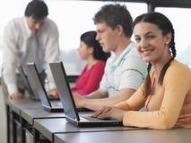 Studenti che utilizzano i computer portatili nella classe del computer Fotografie Stock Libere da Diritti