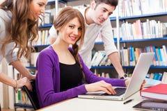 Studenti che utilizzano un computer portatile in una biblioteca Fotografie Stock