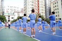 Studenti cinesi allineati per fare ginnastica di radiodiffusione Immagine Stock