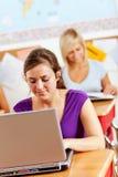 Studenti: Compito scolastico facente teenager sul computer portatile Fotografia Stock Libera da Diritti