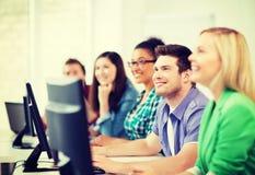 Studenti con i computer che studiano alla scuola Fotografie Stock
