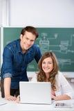 Studenti con il computer portatile allo scrittorio dell'aula Immagine Stock