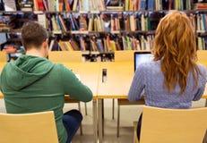 Studenti con il computer portatile ed i libri alla biblioteca immagini stock libere da diritti