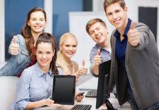 Studenti con il monitor e lo schermo in bianco del pc della compressa Fotografia Stock