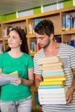 Studenti con il mucchio dei libri nella biblioteca Immagini Stock