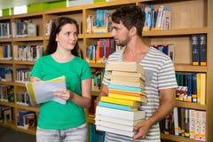 Studenti con il mucchio dei libri nella biblioteca Fotografia Stock