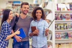 Studenti con l'aggeggio alla libreria Fotografie Stock Libere da Diritti