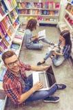 Studenti con l'aggeggio alla libreria Immagine Stock Libera da Diritti