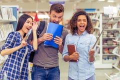 Studenti con l'aggeggio alla libreria Fotografia Stock