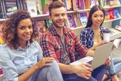 Studenti con l'aggeggio alla libreria Immagini Stock Libere da Diritti