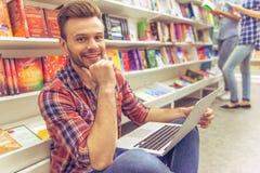 Studenti con l'aggeggio alla libreria Fotografie Stock