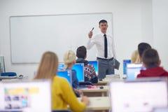 Studenti con l'insegnante nel classrom del laboratorio del computer Immagini Stock Libere da Diritti