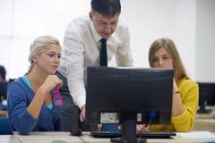 Studenti con l'insegnante nel classrom del laboratorio del computer Immagini Stock