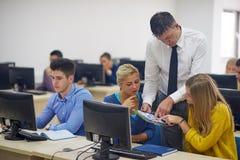 Studenti con l'insegnante nel classrom del laboratorio del computer Immagine Stock