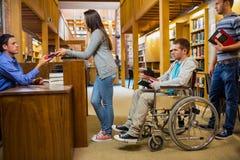 Studenti con l'uomo handicappato nella fila al contatore delle biblioteche Fotografia Stock Libera da Diritti