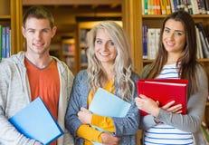 Studenti con le cartelle che stanno contro lo scaffale per libri in biblioteca Immagine Stock
