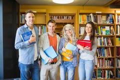 Studenti con le cartelle contro lo scaffale per libri in biblioteca Immagini Stock Libere da Diritti