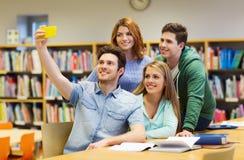 Studenti con lo smartphone che prende selfie alla biblioteca Fotografia Stock Libera da Diritti