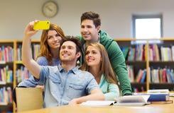 Studenti con lo smartphone che prende selfie in biblioteca Fotografie Stock