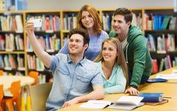 Studenti con lo smartphone che prende selfie in biblioteca Immagini Stock