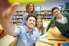 Studenti con lo smartphone che prende selfie in biblioteca Immagine Stock Libera da Diritti