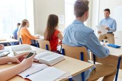 Studenti con lo smartphone e l'insegnante alla scuola Fotografie Stock