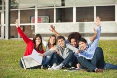 Studenti con seduta sollevata mani all'università Fotografie Stock Libere da Diritti